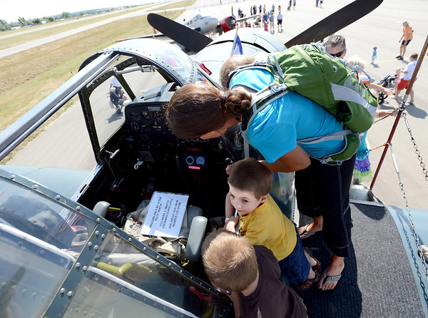 "Jack Wysong, bottom, his brother Cole, and mother Laura Purdew, look into the cockpit of one of the vintage planes at the 7th annual Boulder Airport Day on Saturday.<br /> For more photos and a video of airport day, go to  <a href=""http://www.dailycamera.com"">http://www.dailycamera.com</a>.<br /> Cliff Grassmick / June 16, 2012"