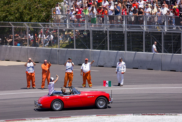 Track workers wave to the passing F1 drivers during the pre-race drivers' parade.