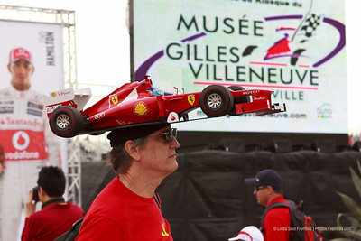 There are F1 fans, and then there's this guy. Yes, that's a replica Ferrari F1 car on his head.