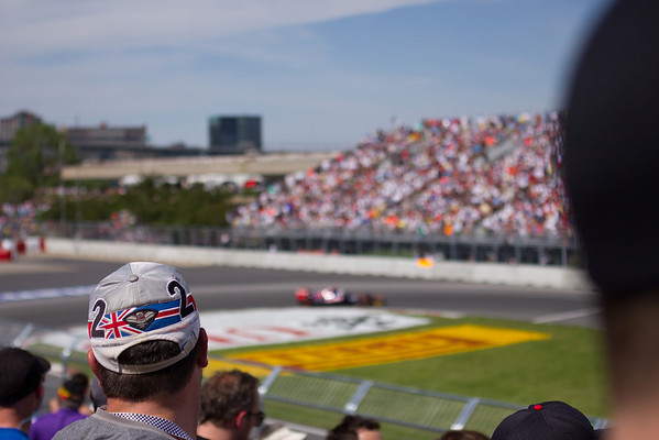 A fan watches the race, decked out in a pretty cool McLaren Mercedes hat.