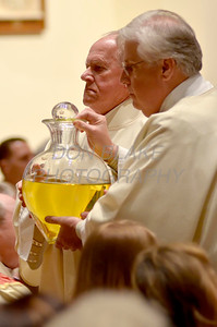 Deacons Frank Quinlan (left) and Thomas Halko carry the oils after the blessing during the Chrism Mass at Holy Cross Church in Dover, Del., Monday, April 2, 2012. photo/www.DonBlakePhotography.com