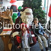 Graham, 3, and Jack Burkert, 6, pose with Santa Claus at Unique and More during the Christmas Walk on Sunday. • Natalie Conrad/Clinton Herald