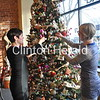 Painted Rooster owners Erin George and Emily Steenhard arrange ornaments on their tree during the Christmas Walk on Sunday. Local retailers benefitted from booming business throughout the event by partnering together. • Natalie Conrad/Clinton Herald