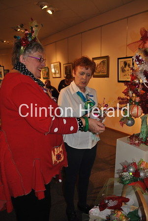 Artist Karla Byl shows fellow artist Bonnie Temperly her unique Christmas tree creation at River Arts Center during the Christmas Walk on Sunday. The center featured unique decorations and gifts from local artists. • Natalie Conrad/Clinton Herald