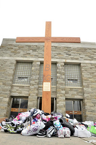 Donated shoes lay at the foot of the cross at St. Anthony of Padua Parish in Wilmington, Del., during the 2012 Cross Pilgrimage March 31, 2012. photo/ www.DonBlakePhotography.com