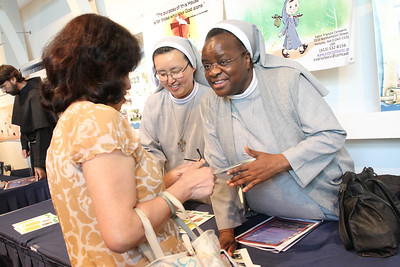 Franciscan Missionary Sisters of Assisi Regina Mulenga, right and Sofia Lee speak with a woman making inquiries at their table.