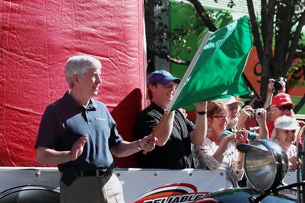 Record-Eagle/Keith King<br /> Gov. Rick Snyder waves a green flag on Front Street in Traverse City Saturday, June 23, 2012 at the start of the 2012 Great Race which is approximately 2,283 miles over the span of nine days, taking racers around the Great Lakes, through Canada, and finishing in Dearborn, MI.