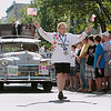 Record-Eagle/Keith King<br /> Tevie Smith, of Vancouver, BC, Canada, waves an American and Canadian flag on Front Street in Traverse City in front of the 1947 Chrysler he'll drive Saturday, June 23, 2012 during the 2012 Great Race which is approximately 2,283 miles over the span of nine days, taking racers around the Great Lakes, through Canada, and finishing in Dearborn, MI.