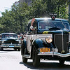 Record-Eagle/Keith King<br /> Competitors and their vehicles, including the 1936 Ford Fordor Deluxe Police Car, at right, make their way to the start on Front Street in Traverse City Saturday, June 23, 2012 during the 2012 Great Race which is approximately 2,283 miles over the span of nine days, taking racers around the Great Lakes, through Canada, and finishing in Dearborn, MI.