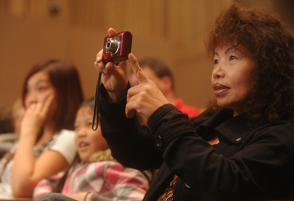 Globe/Roger Nomer<br /> Wendy Moua takes a photo of her daughter Alisa on stage during Wednesday's Spelling Bee.