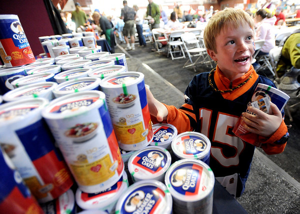 """Jack Ahrens, 7, grabs some oatmeal for home after eating it at the 16th Annual Lafayette Oatmeal Festival on Saturday.<br /> For more photos and a video of the festival, go to  <a href=""""http://www.dailycamera.com"""">http://www.dailycamera.com</a>.<br /> January 14, 2012 / Cliff Grassmick"""