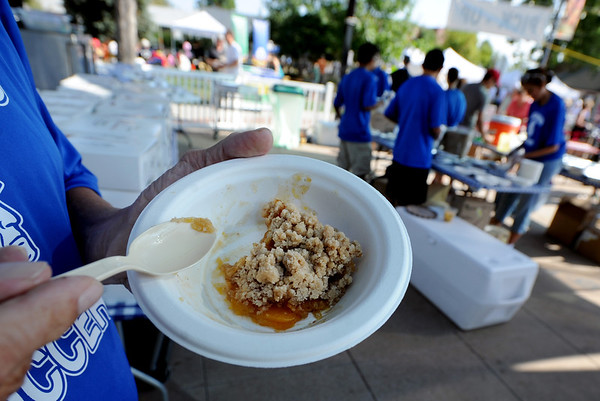 "Ken Ebersole eats his peach cobbler while Centaurus High School soccer players make peach smoothies  during the Lafayette Peach Festival on Saturday.<br /> For more photos and a video from the Peach festival, go to  <a href=""http://www.dailycamera.com"">http://www.dailycamera.com</a>.<br /> Cliff Grassmick  / August 18, 2012"