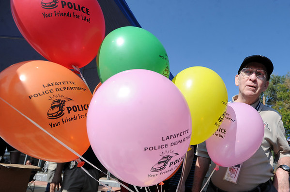 "Daryl Smith hands out balloons for the Lafayette Police Department.<br /> For more photos and a video from the Peach festival, go to  <a href=""http://www.dailycamera.com"">http://www.dailycamera.com</a>.<br /> Cliff Grassmick  / August 18, 2012"