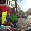 Record-Eagle/Jan-Michael Stump<br /> From left, Barb Schmuckal, her granddaughter Hannah Belvin, 6, grandson Beau Belvin, 3 and daughter Amber Belvin (cq) hold up signs for the floats in Thursday's National Cherry Festival Junior Royale Parade in downtown Traverse City.