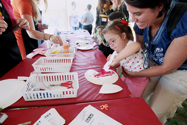 Record-Eagle/Keith King<br /> Grace Middlebrook, 4, of Cedar Springs, is held by her mother, Sara Middlebrook, as Grace paints an art project at the KidzArt and Artists Creating Together (ACT) station Wednesday, July 11, 2012 during the National Cherry Festival Special Kids Day at the Open Space.