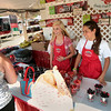 Record-Eagle/Keith King<br /> Becca Pensyl, left, 15, and Marissa Ingersoll, 18, assist a customer with cherries at an Edmondson Orchards booth Thursday, July 12, 2012 during the National Cherry Festival.