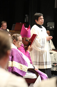 With a prayerful kiss of peace, Archbishop Wilton D. Gregory acknowledges the names in the Book of the Elect during the presentation of the catechumens.