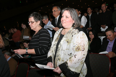 During the call to continuing conversion Holy Cross Church candidate Joan Haddad, center, stands with her sponsor Kathy Szabo.
