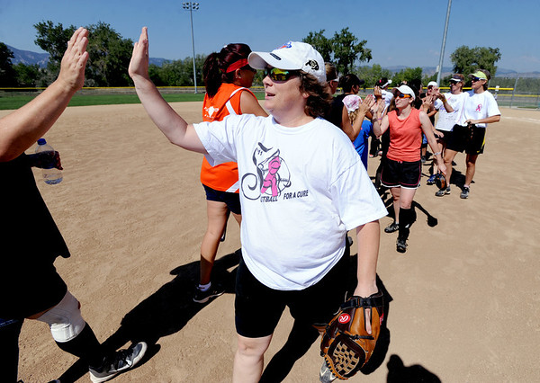 "Cancer survivor, Heidi Muller, congratulates the Orange Slices team members after a benefit softball game at Stazio Fields in Boulder on Sunday.<br /> Izzy Crouse started a softball tournament to raise money to help fight breast cancer after her teammate, Heidi Muller contracted the disease.<br /> For a video and more photos of the softball, go to  <a href=""http://www.dailycamera.com"">http://www.dailycamera.com</a>.<br /> Cliff Grassmick  / August 12, 2012"