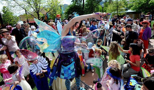 """Elana McMaster,  Lily the Blue Fairy, makes giant bubbles for the elves and fairies below.<br /> Downtown Boulder held the popular Tulip Fairy and Elf Parade on the Pearl Street Mall on Saturday.<br /> For  a video and more photos of the event, go to  <a href=""""http://www.dailycamera.com"""">http://www.dailycamera.com</a><br /> Cliff Grassmick / April 28, 2012"""