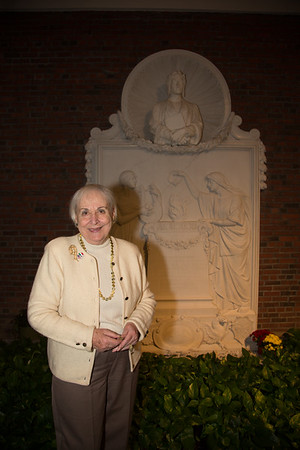 Terri Mazzulli in front of the white marble bas-relief of Dante Alighieri.