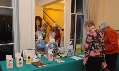 """Board members of the Elmhurst Heritage Foundation (left) Cheryl Kopecky and Cathy Jordan look through the auctioned items during the  """"Meet Me At The Fair"""" wine and beer tasting held at Wilder Mansion through the Elmhurst Heritage Foundation Thursday October 25, 2012.  Staff photo by Erica Benson"""
