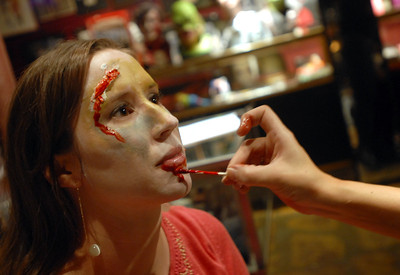 Amy Browne of Berwyn gets her face painted by Heidi Ruehle of Oak Park prior to the Zombie Walk and Pub Crawl sponsored by Horrobles in Berwyn Saturday October 27, 2012.  Makeup artists paint participants faces for the event.   Staff photo by Erica Benson   |    Buy this photo at snapshots.mysuburbanlife.com/1558190
