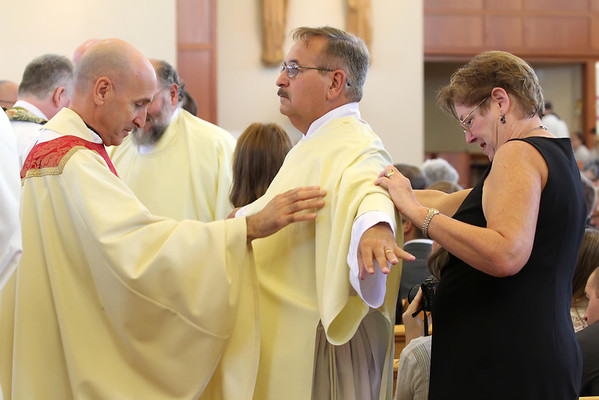 The Fr. Roger DiBuo helps vest candidate Barry Taylor along with Barry's wife Jeanette during his Ordination to the Diaconate at St. Margaret of Scotland Church, August 24, 2013. wwwDonBlakePhotography.com