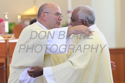 Candidates P. Michael Olliver (left) and Austin Lobo give each other the Kiss of Peace during their Ordination to the Diaconate at St. Margaret of Scotland Church, August 24, 2013. wwwDonBlakePhotography.com