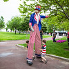 Kids walk between Uncle Sams stilt legs