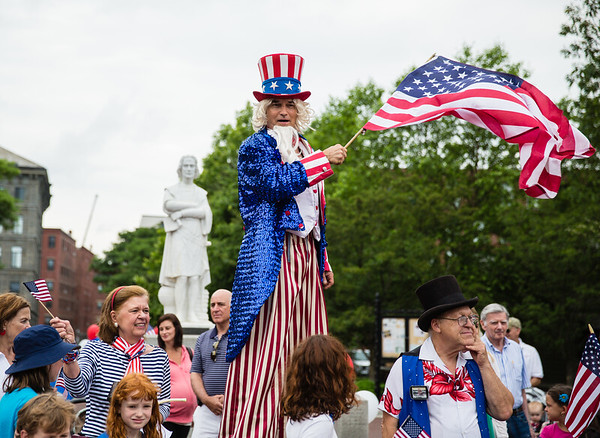 Uncle Sam on Stilts waves the flag at Christopher Columbus Park