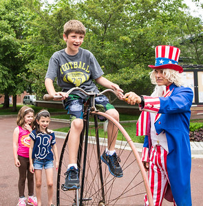 Daniel takes a ride on the monster bike helped by Uncle Sam