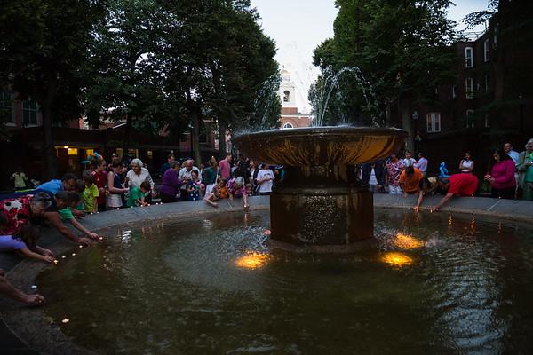 Neighbors set candles into the Prado Fountain