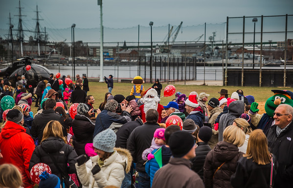 Crowds swarm Santa Claus after he arrives via helicopter at Puopolo Field