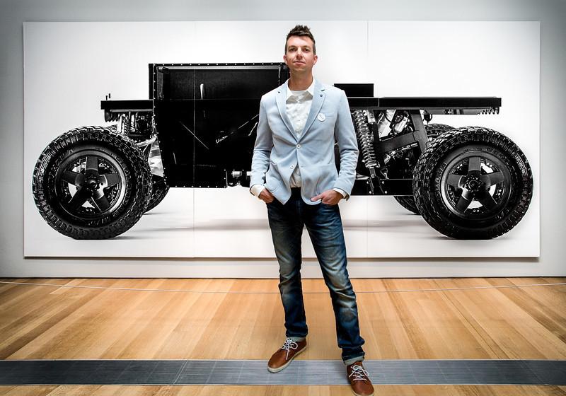 Joey Ruiter, KCAD Industrial Design Alumnus, in front of a photo of his Reboot Buggy.