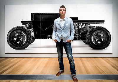 Joey Ruiter, KCAD Industrial Design Alumnus, in front of a photo of his Reboot Buggy.