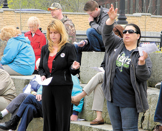 Dan Irwin/NEWS<br /> Denise Fuller, left, and Kristine Koukis extend hands in praise during yesterday's National Day of Prayer service at Riverwalk Park.
