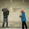Reporters tape a broadcast with the newly reinforced side panel brackets shown on the wall.