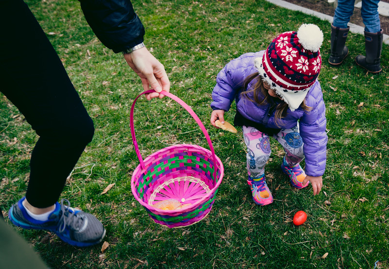 Little girl finds an egg at the Easter Egg hunt in the park