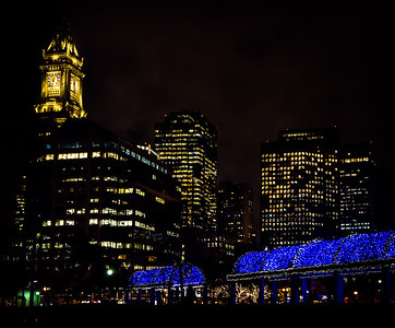 Iconic blue lights at Christopher Columbus Park with Boston skyline.