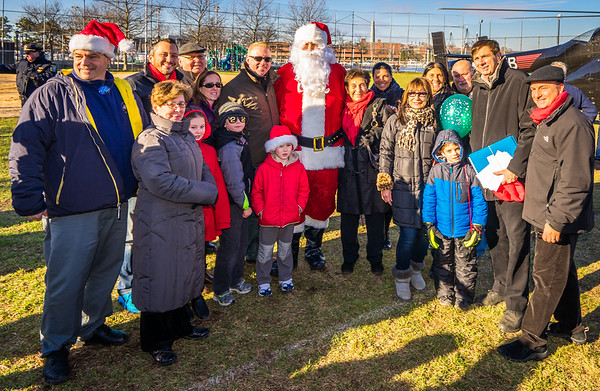 After emerging from his helicopter, Santa is joined by the Pallotta Family, NEAA leaders and local officials