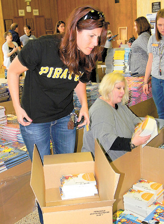 Dan Irwin/NEWS<br /> Jill Trott ofCray Horizons, left, and Sue Ellen Patton of Neshannock Memorial School sort examine some of the 400,000 free books being made available to Mercer and Lawrence county teachers yesterday at Westminster College.