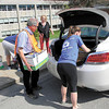 Volunteers help load boxes of free books into a teacher's car. — Dan Irwin