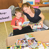 Dan Irwin/NEWS<br /> With the help of her son, Jack, Casey Pataki chooses free books for Lawrence County Comnunity Action Partnership yesterday in the lobby of Westminster College's Orr Auditorium.