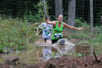 Jen Carmean(front), and Rj Jones(back) running through the final mud pit to finish the race.