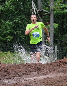 The second place winner of the race, Douglas Metcalfe, runs through the mud on his way to the finish.
