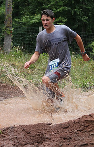 Third place winner, Aj Turpin, runs through the deep muddy mess to get to the finish line, later also winning fastest male time in his age bracket.
