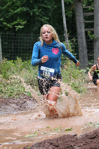 Participants run in the rain through the mud pit at the Hard to the Core 5k Mud Run.