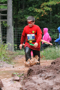 Isaac Reppert battles through the mud in a Robin super hero costume.