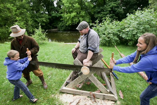 Record-Eagle/Keith King<br /> Chance Anderson, left, 7, of Comstock Park, and his mother, Linda Anderson, use a two-man cross-cut saw to cut a log as Craig Kasmer, back left, with Hartwick Pines State Park, assists and Ken Bauer, back right, also with Hartwick Pines State Park, looks on, as part of the Heritage Day Old Fashioned Picnic during the National Cherry Festival.